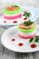 Colored rice on plates on napkin on wooden table photo
