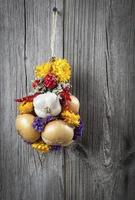 Braided bunch with onions, garlic and flowers photo