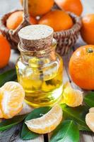 Bottle of essential citrus oil and ripe tangerines in basket