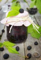 Blackberry jam in jar and berries on wooden table