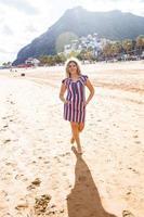 Beautiful girl in the beach running photo