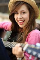 Young woman sitting with a guitar photo