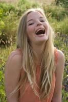 Teenage girl laughing outdoors photo