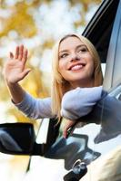 Woman waving from car window photo