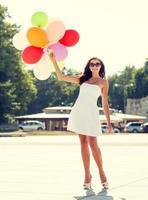 sonriente mujer joven en gafas de sol con globos