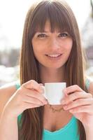 sonriente joven bebiendo café expreso en camiseta turquesa foto