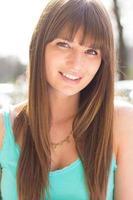 mujer joven sonriendo en camiseta turquesa