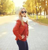 Fashion blonde woman wearing a sunglasses and red leather jacket