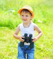 Happy child boy with binoculars outdoors in summer day