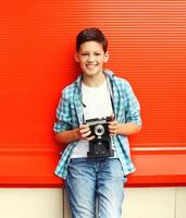 Happy smiling little boy teenager with retro vintage camera