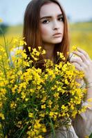 Portrait of beautiful woman with yellow flowers in the field