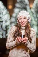 jonge vrouw met een koptelefoon en hete thee buitenshuis