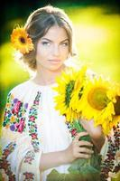 Young girl wearing Romanian traditional blouse holding sunflowers