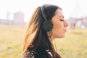 jonge mooie vrouw die aan muziek met hoofdtelefoons luistert