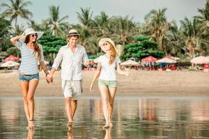 Group of happy young people walking along the beach on photo