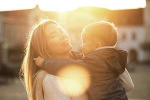 felicidade mãe e filho na rua em dia de sol.