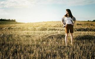 young beautiful free lonely woman walks across field photo
