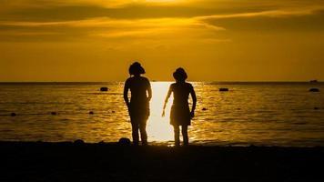 Feliz mujer silueta de pie contra la puesta de sol con los brazos alzados foto