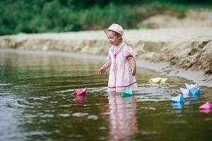 girl plays with paper boats in river