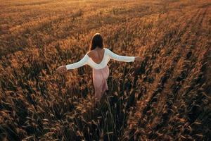 bella dama morena en campo de trigo al atardecer