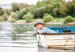 Little boy in old boat on the calm lake surface photo