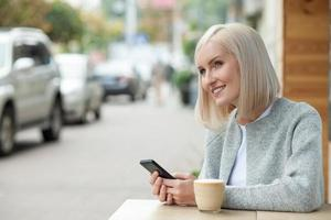 Cheerful blond woman with telephone in cafe