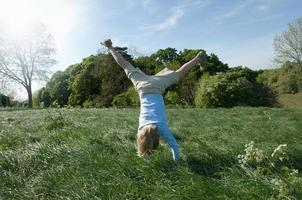 Boy doing handstand in field photo