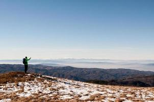 Hiker taking photo with digital camera on mountain