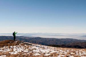 Foto de excursionista tomando con cámara digital en montaña