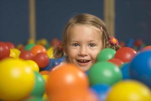 Retrato de una niña sonriente en una piscina de bolas foto