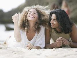 pareja joven tumbado en la playa y sonriendo