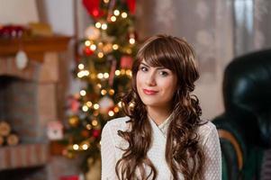 retrato de mulher jovem sorridente perto de árvore de Natal