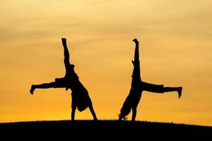 Brother and sister doing cartwheels.