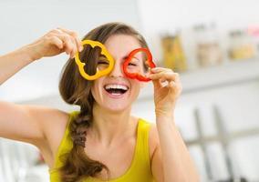 mujer joven divertida que muestra rodajas de pimiento foto