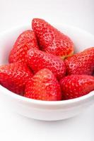 Strawberries in a bowl isolated on white background.