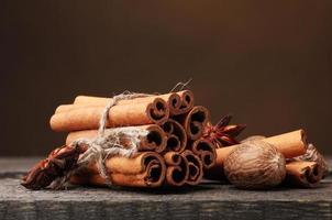 Cinnamon sticks, nutmeg and anise on wooden table photo