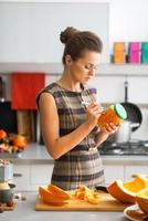 young housewife signing jar of pickled pumpkin in kitchen