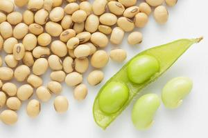 fresh pea pod and dry soybean on white background.