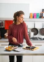 Thoughtful young housewife with pan of baked pumpkin in kitchen