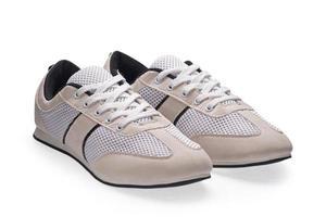 par de zapatos deportivos blancos con cordones foto