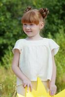 Image of lovely red-haired girl posing in park photo