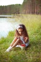 Happy beautiful little girl in white dress with strawberry outdoors photo