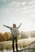 happy beautiful girl walks on river bank early in morning photo