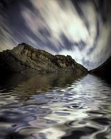 rock mountain with slow motion cloud reflected on lake