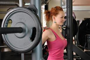 young girl doing squats with barbell photo