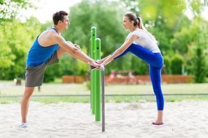 Pareja haciendo ejercicios de estiramiento en el parque