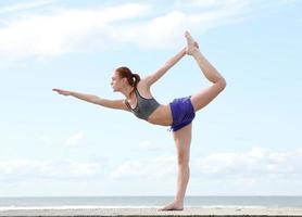 joven mujer equilibrada sobre una pierna en posición de yoga