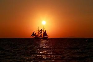 The sun setting over a sailing ship in Santorini.