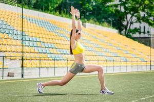Entrenamiento exitoso. mujer en chándal hace entrenamiento en el fie