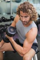 Young man exercising with dumbbell in gym photo